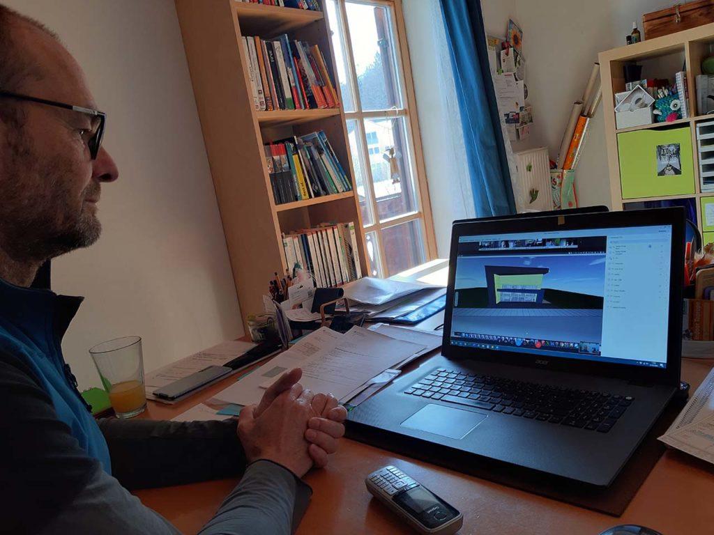 Achim schaut auf den Bildschirm der die Ansicht der Kletterhalle zeigt