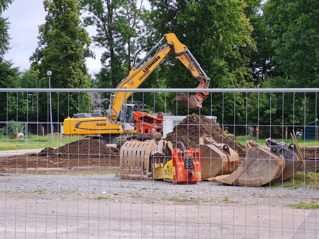 Bauzaun, Bagger, Baumaschinen auf dem Gelände der zukünftigen Kletterhalle